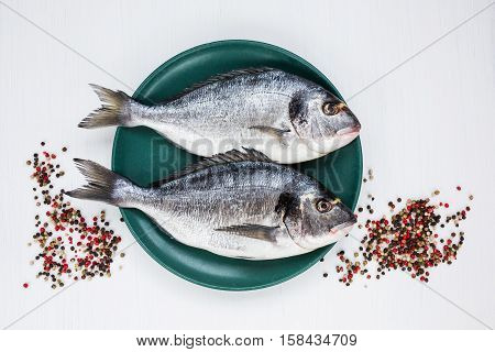 Raw Dorado Fish On Yellow Plate With Peppercorns On White Table. Top View, Copy Space