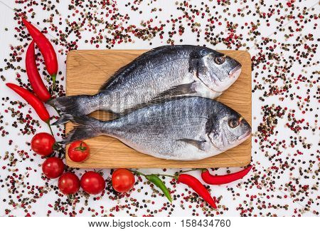 Raw Dorado Fish On Wooden Cutting Board With Vegetables. Top View, Copy Space