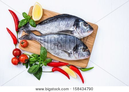 Raw Dorado Fish On Wooden Cutting Board With Vegetables On White Table. Top View, Copy Space