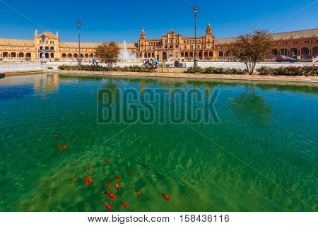 Spain Square or Plaza de Espana in Seville in the sunny summer day, Andalusia, Spain. Goldfish in the channel on the foreground