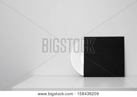 white vinyl record in black paper case put on table and leaning against a wall
