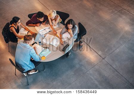 Multiracial group of young students studying together. High angle shot of young people sitting at the table and studying on laptop computer.