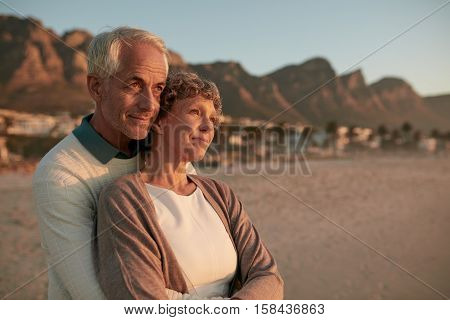 Elderly Couple Standing Together And Embracing On The Beach