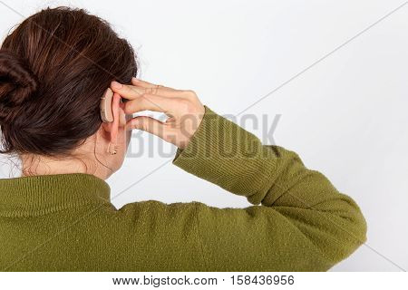 The Woman inserting her brown hearing aid