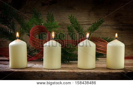 Four white burning candles on the fourth advent decorated with spruce twigs and a red ribbon on a rustic wooden board