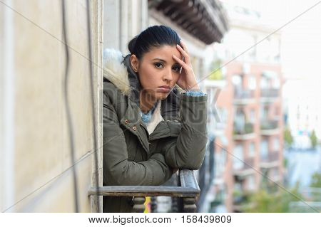young beautiful sad and desperate hispanic woman in winter coat suffering depression looking thoughtful and frustrated at apartment balcony looking depressed at the street