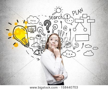 Thinking blond woman is standing near a concrete wall with a business plan depicted on it. Concept of strategy