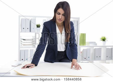Portrait of a centered woman architect working with blueprints in her office. She is standing near her table and looking at them