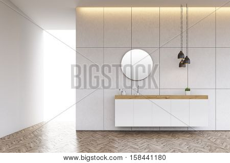 Bathroom interior with a tiled wall a round mirror and a long sink counter. 3d rendering.