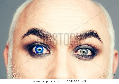 Senior man with blue color lens in eye and bushy eyebrows on old wrinkled face on grey wall