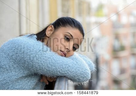 young beautiful sad and desperate hispanic woman suffering depression looking thoughtful and frustrated at apartment balcony looking depressed at the street