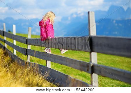 Cute Little Girl Sitting On Wooden Fence Admiring Beautiful Landscape In Dolomites Mountain Range