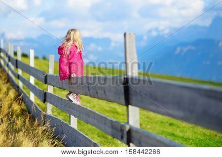 Cute Little Girl Sitting On Wooden Fence Admiring Beautiful Landscape In Dolomites Mountain Range