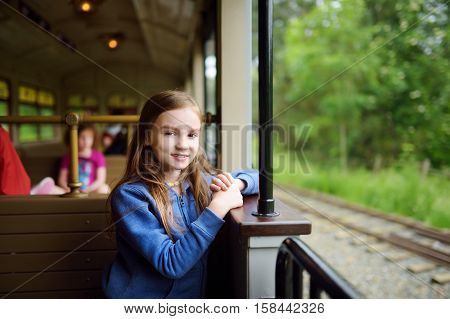Happy Little Girl Riding A Train In A Theme Park Or Funfair