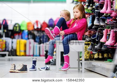 Two Little Sisters Choosing And Trying On New Rain Boots