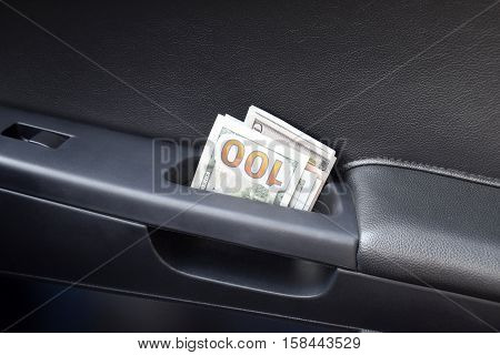 Several Notes Of Us Dollars And Are Folded In Half In The Door Handle Of The Car. The Money In The C