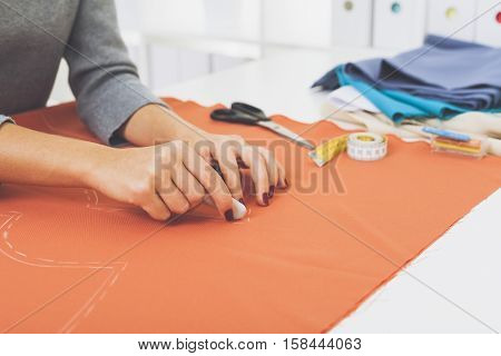 Close up of woman's hands in gray sweater. She is drawing a pattern at an orange piece of tissue