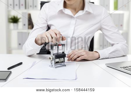 Close up of a woman in white blouse who is sitting in the office and stamping a document. Concept of notary work