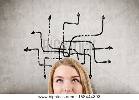 Close up of a blond woman's head near a concrete wall with an arrow labyrinth sketch on it. Concept of looking for the way out
