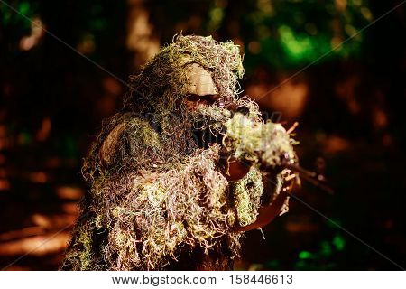 Sniper man or war soldier wears ghillie suit military clothing camouflage with sniping rifle on natural environment background