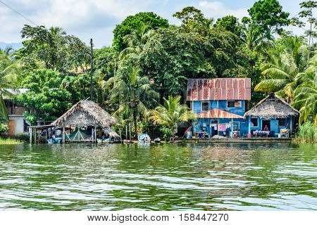 Rio Dulce, Guatemala - September 1 2016: Wooden houses with tin & palm leaf roofs on riverbank of the Rio Dulce in Guatemala, Central America