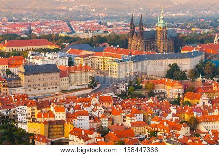 Prague Castle complex with gothic St Vitus Cathedral in the evening time illuminated by sunset, Hradcany, Prague, Czech Republic. UNESCO World Heritage. Aerial shot from Petrin Tower.