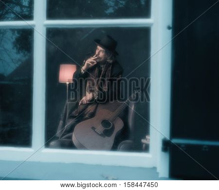 Cigarette Smoking Vintage 1970S Guitarist Leaning On Back Of Chair Behind Window.