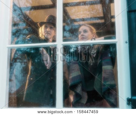 Pensive Vintage 1970S Musicians Standing Behind Rainy Window Looking Outside.