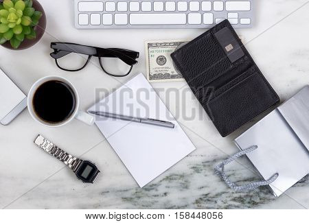 Overhead view of office desktop with computer keyboard cell phone shopping bag wallet money pen paper reading glasses coffee and plant on marble surface. Shopping on line concept.