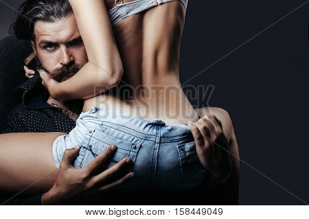 bearded handsome man and female slim flexible body of young pretty woman or girl with sexy buttocks in jeans shorts on grey background