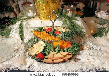 Holiday table setting of serving dishes holding sliced cheeses and strawberries.