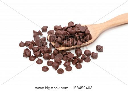 Chocolate morsels on wooden spoon isolate on white