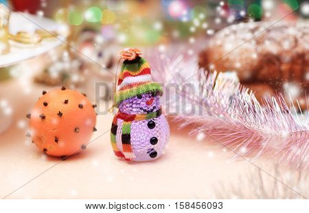 Christmas and new year background. toy snowman and a beautifully decorated orange Christmas table. the photo has a empty space for your text