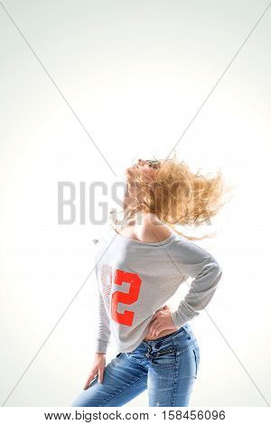 stylish young blond woman in jeans and blouse on a grey background