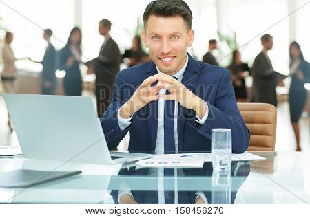 businessman at the workplace. working with financial documents. in the workplace is an open laptop and a glass of water. Photo on the background of office