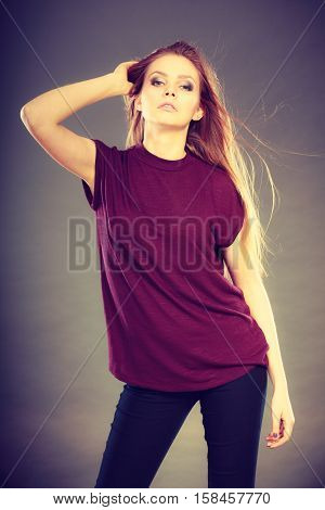 Haircare beauty hairstyling concept. Portrait of young attractive brunette woman wearing dark tshirt holding her beautiful long brown hair.