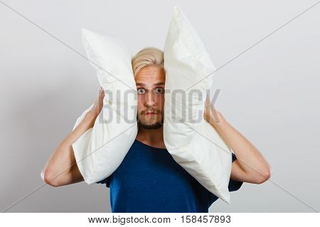 Man need silence. Sad tired young male closing ears with pillows protecting from loud noise have head pain. Guy not wanting to listen or can not sleep