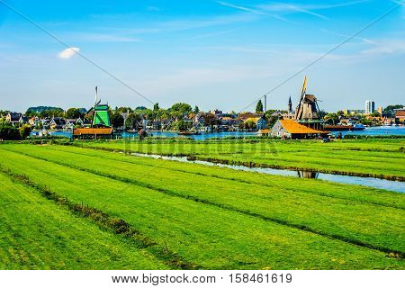 Typical Dutch Landscape with open Fields, Canals and Dutch Windmills at the Historic Village of Zaanse Schans in the Netherlands