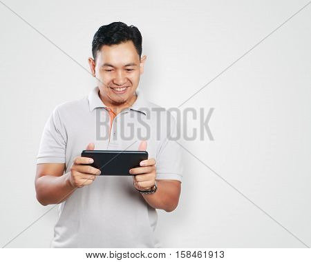 Photo image portrait of a cute handsome young Asian man with funny face playing games on tablet