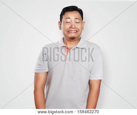 Photo image portrait of a cute handsome young Asian man crying in pain and looking down painful gesture