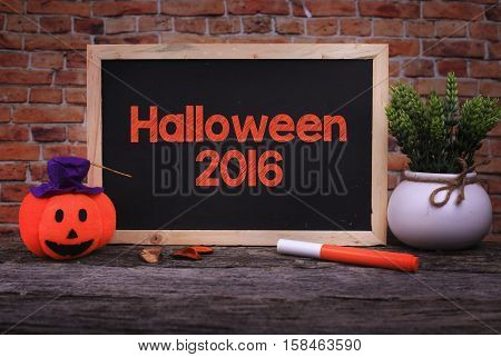 Pumpkin Head Candle and a Chalkboard written Halloween 2016 on wooden background