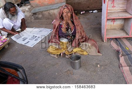 PUSHKAR, INDIA - FEBRUARY 17: Unidentified old indian beggar waits for alms on a street on the ghat along the sacred Sarovar lake in Pushkar, India on February 17, 2016.