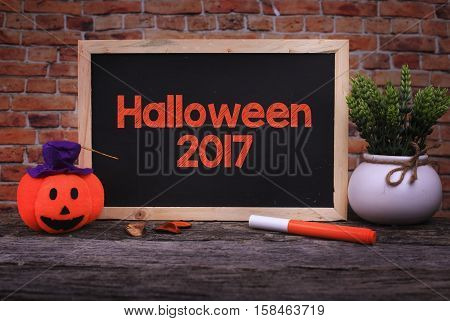 Pumpkin Head Candle and a Chalkboard written Halloween 2017 on wooden background