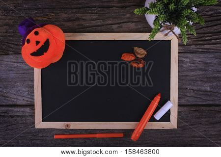Pumpkin Head Candle and a Chalkboard with copyspace area on wooden background
