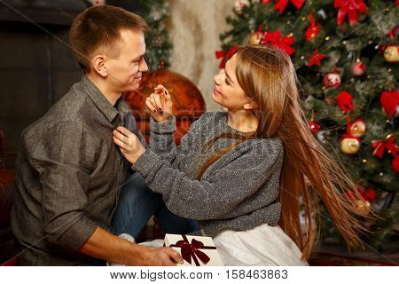Loving couple and Christmas. Girl unbuttoning shirt guy. In the background a beautiful Christmas tree.