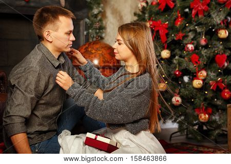 Loving couple and Christmas. Girl unbutton shirt guy. In the background a beautiful Christmas tree.