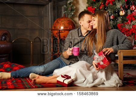 Loving couple and Christmas. Girl and a guy sitting on floor near the fireplace. She is holding Christmas gift. He drinks hot Christmas drink cocoa with marshmallows. In background beautiful Christmas tree.