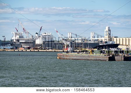 NEW YORK,USA - AUGUST 22,2016 : Pontoons, tugboats and cranes unloading a cargo ship at the New York Harbor