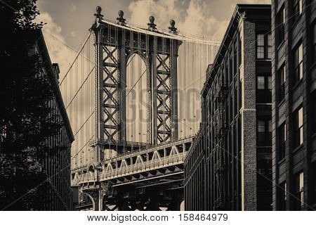 Vintage toned famous view of the Manhattan Bridge and a Brooklyn street sidelined by old brick buildings in New York City