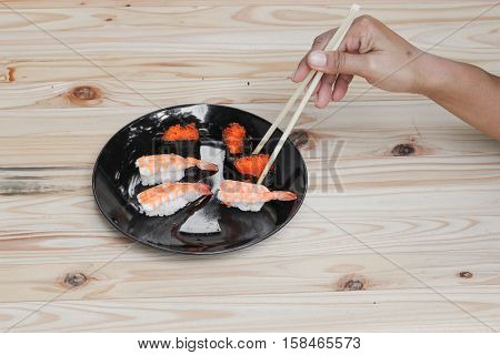hand holding sushi chopsticks on a black plate wooden table background